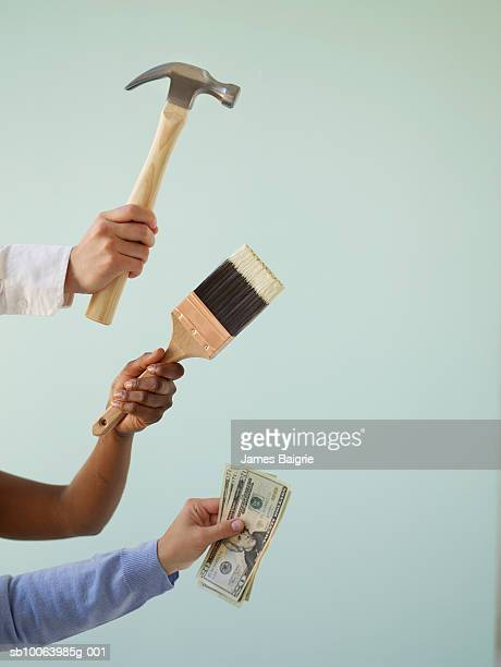 three people holding paintbrush, hammer and money, close-up of hands - erin james stock-fotos und bilder