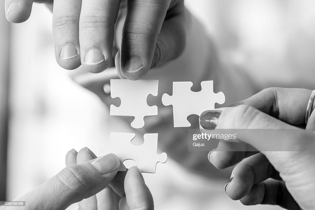 Three people holding puzzle pieces to match them : Stock Photo