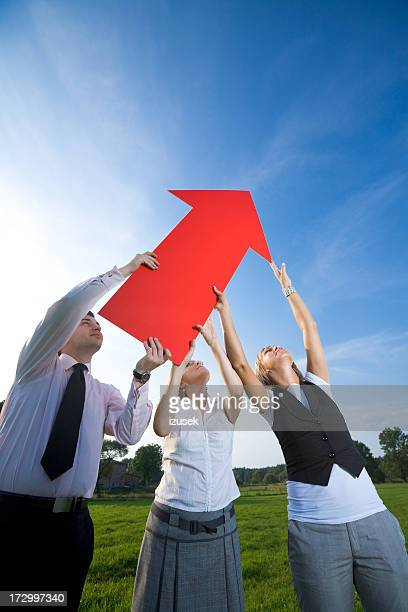 Three people holding red arrow