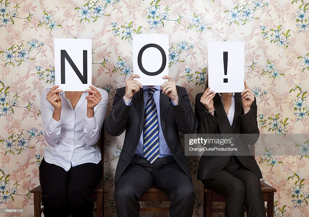 Three people holding the word NO! over their faces : Stock Photo