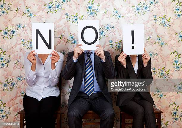 three people holding the word no! over their faces - dismissal stock photos and pictures