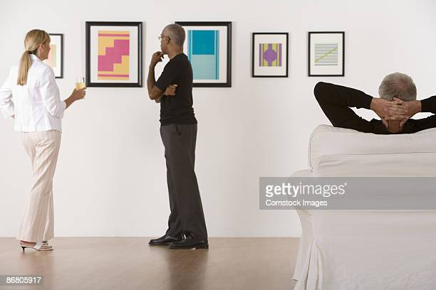 Three people in an art gallery viewing paintings.