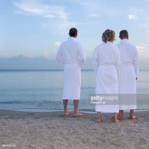 Three People in Bathrobes Standing on Beach