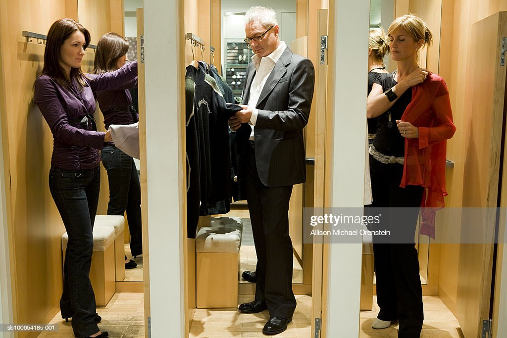 Three people in dressing rooms trying on clothes : Foto stock