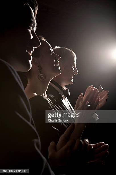 Three people in formal wear clapping hands