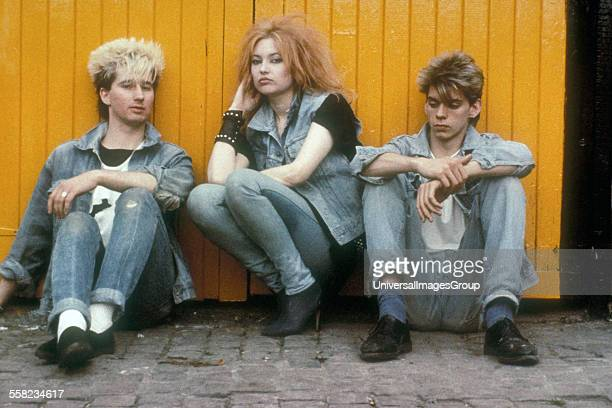 Three people in Post Punk styles resting against a yellow fence UK 1980