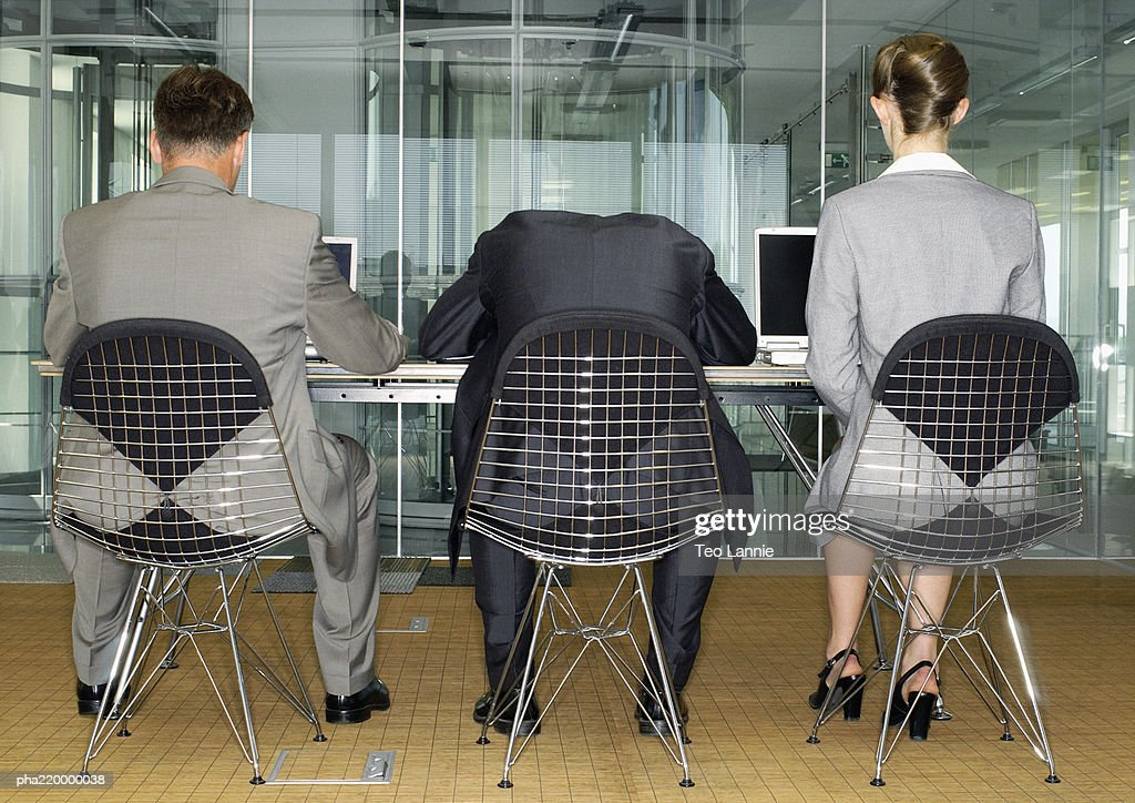 Three people in suits, using laptops, one has head on table, rear view. : Stockfoto