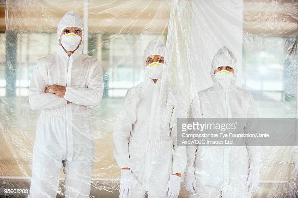 "three people in surgical masks and white suits - ""compassionate eye"" stock pictures, royalty-free photos & images"