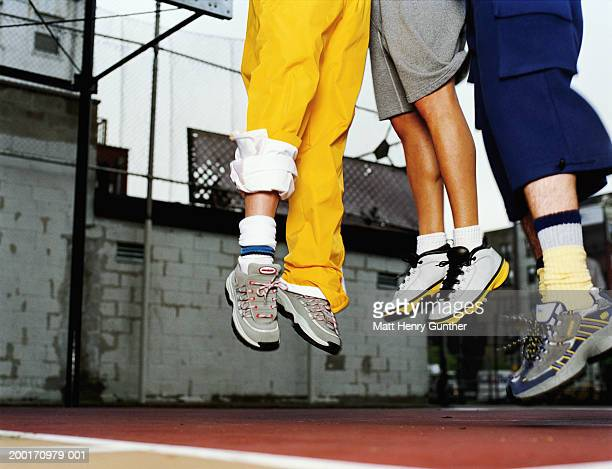 three people jumping in air on basketball court, low section - tracksuit bottoms stock pictures, royalty-free photos & images