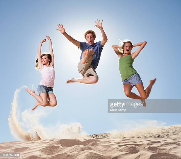 Three people jumping in the sand