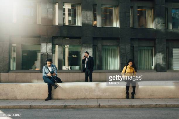 three people keeping social distancing working outdoors - distante foto e immagini stock
