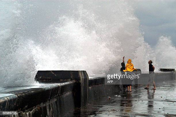 Three people look at huge waves lashing Havana's malecon 23 October 2005 as Hurricane Wilma batters the wets side of the island where more than half...