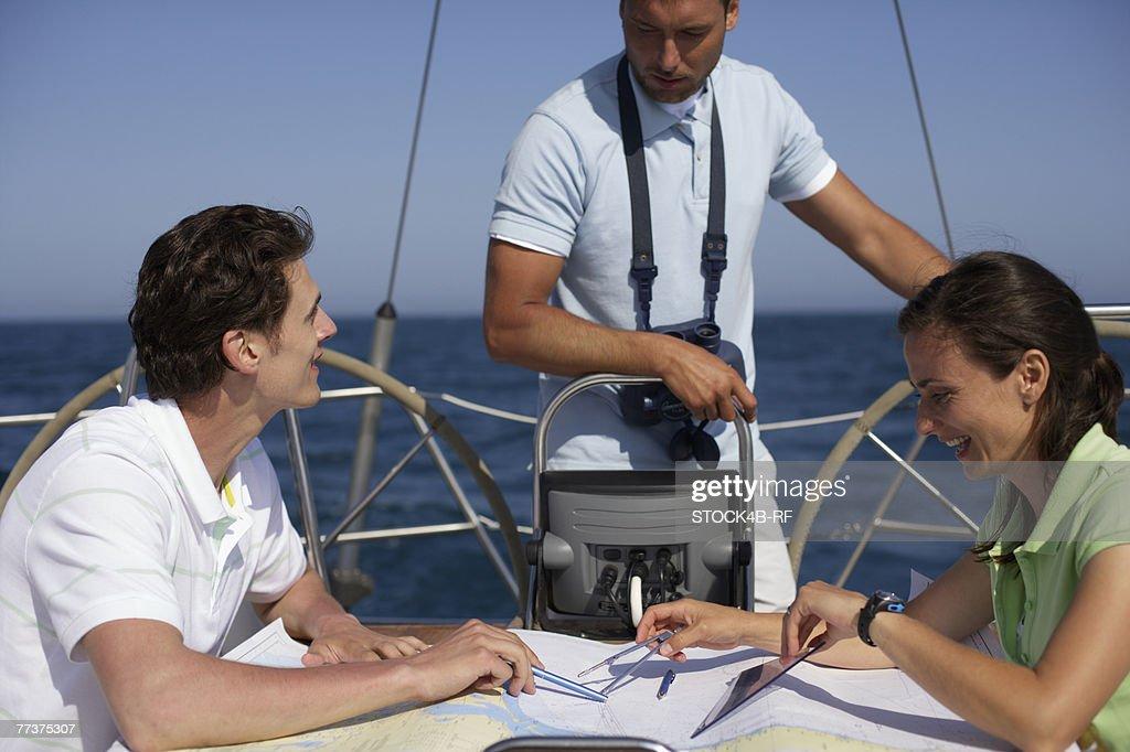 Three people navigating : Stock Photo