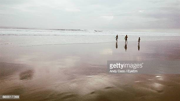 three people on idyllic beach in indonesia - wide shot stock pictures, royalty-free photos & images