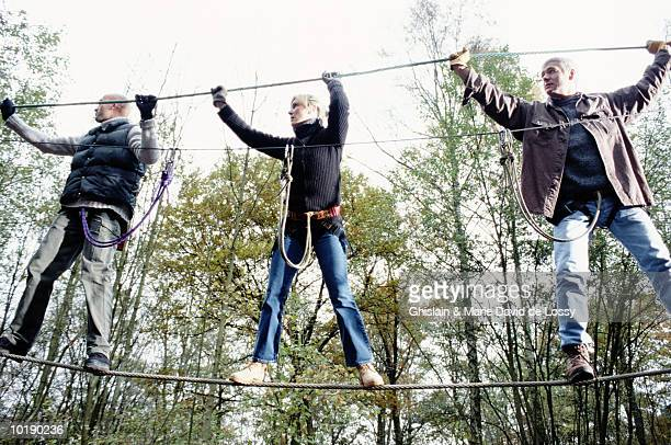 Three people on monkey bridge