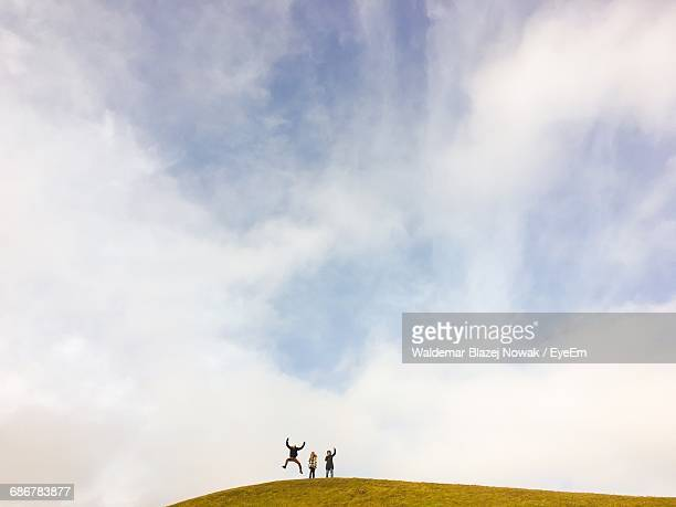three people on mountain against cloudy sky - pomorskie province stock photos and pictures