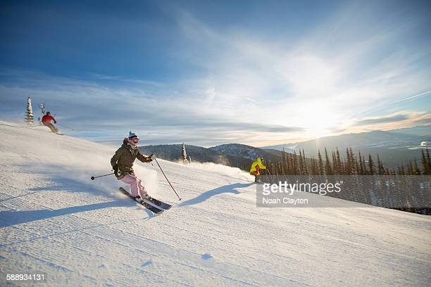three people on ski slope at sunlight - ski resort stock pictures, royalty-free photos & images