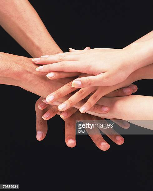 Three people piling hands