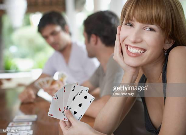 Drei Personen Spielkarten auf einem Tisch, an dem die Frau