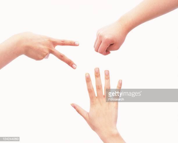 Three people playing rock-scissors-paper