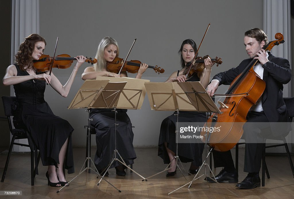 Three people playing violins and one playing cello : Stock Photo