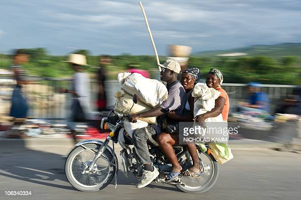 Three people ride a motorcycle at the weekly market on a bridge over the Artibonite river whose waters are believed to be the source of Haiti's...