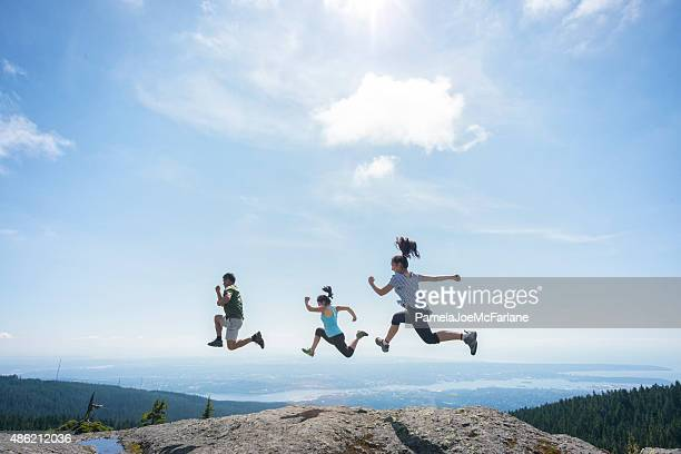 three people running and jumping on mountain top, cliff edge - vancouver canada stock pictures, royalty-free photos & images
