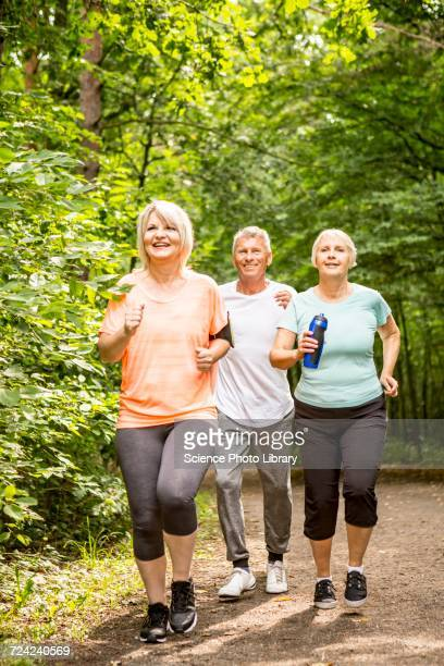 Three people running on track in woods