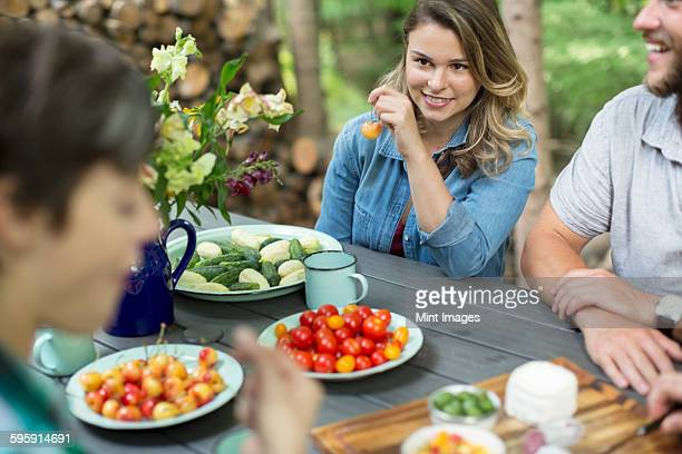 Three people seated at a table outdoors, with fresh fruit and vegetables in plates on the table.