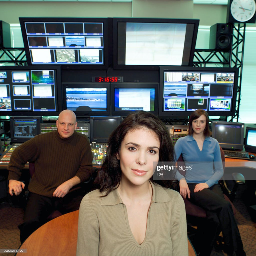Three people seated in television control room : Stock Photo