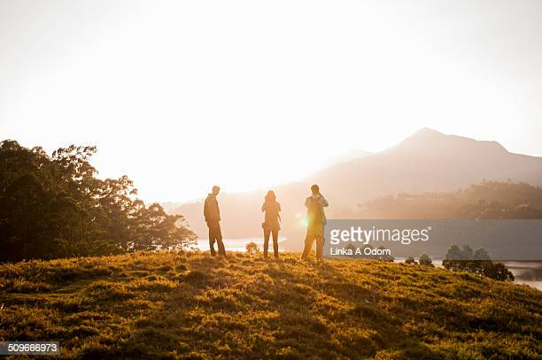 Three people silhouetted by a golden sunset.