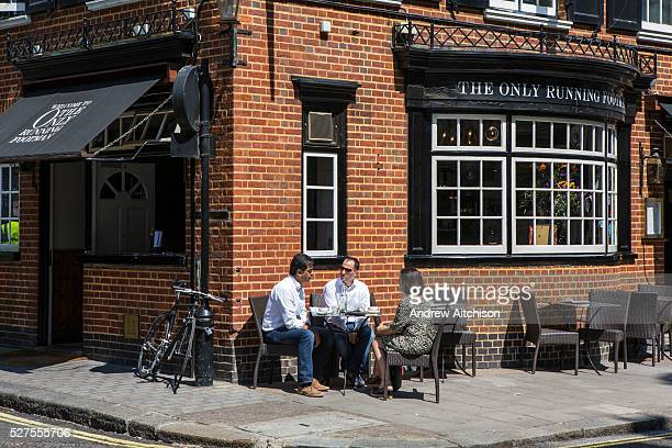 Three people sit outside The Only Running Footman gastro pub/restaurant on Charles Street Mayfair London United Kingdom It is described as a...