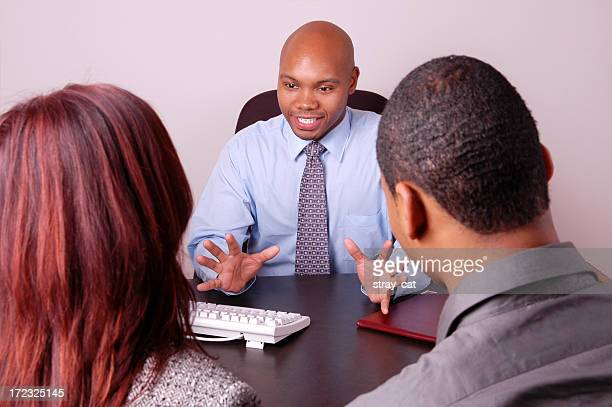 Three people sitting at a business desk, talking