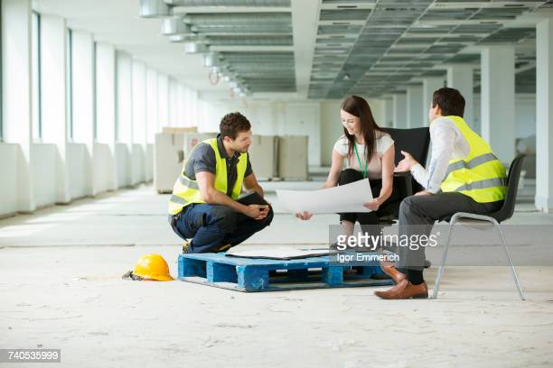Three people sitting in newly constructed office space, looking at construction plans