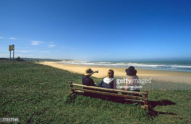 three people sitting on a bench looking out to sea. hamburg, eastern cape province, south africa - eastern cape stock pictures, royalty-free photos & images