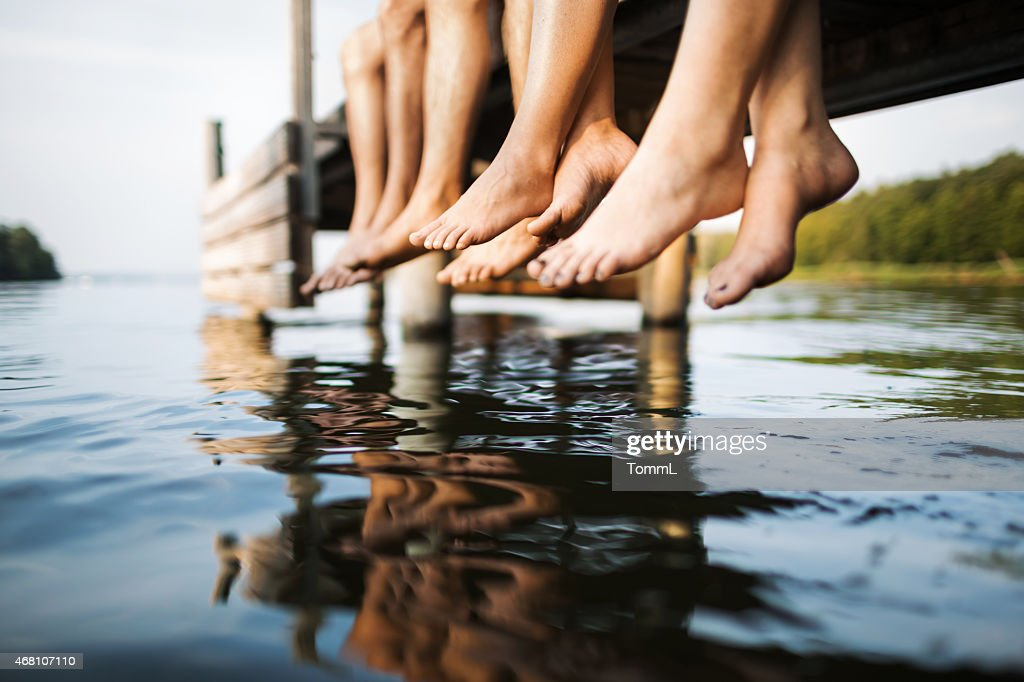 three people sitting on a jetty : Stock Photo