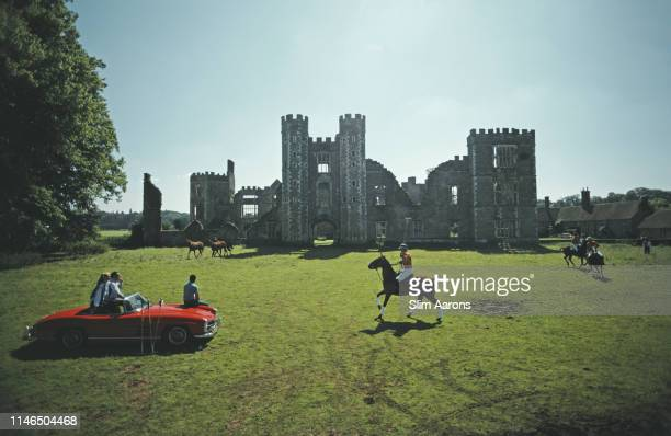Three people sitting on a red Mercedes convertible watch polo players in action at Cowdray Park, West Sussex, August 1985. In the background are the...