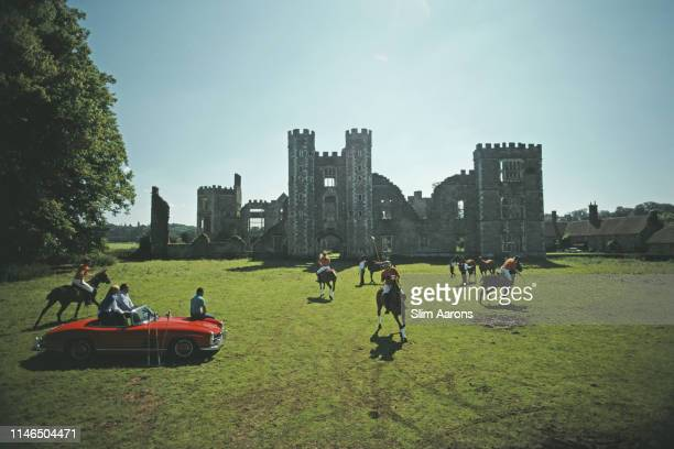 Three people sitting on a red Mercedes convertible watch polo players in action at Cowdray Park West Sussex August 1985 In the background are the...