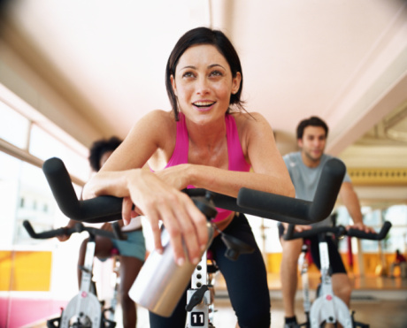 Three people sitting on exercising bikes in gym, close-up - gettyimageskorea