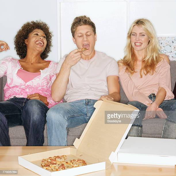Three people sitting on sofa eating pizza