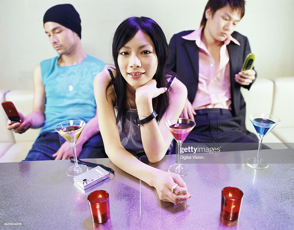 Three People Sitting on Sofa, Men Texting on Their Mobile Phones : Stock Photo
