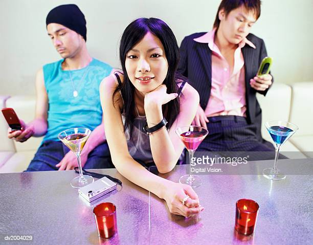 three people sitting on sofa, men texting on their mobile phones - clubkleding stockfoto's en -beelden
