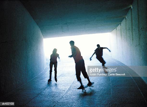Three people skating through tunnel