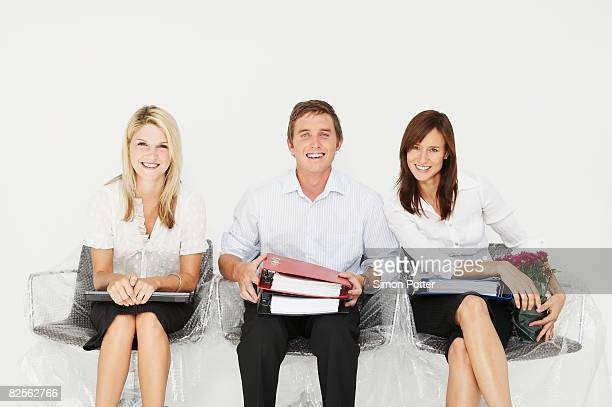Three people smiling in new office
