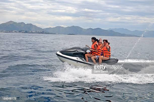 Three people speeding on a jet ski