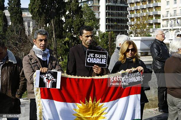 SQUARE ATHENS ATTICA GREECE Three people stand with 'Je suis Charlie' poster behind a large Kurdish flag A second vigil by Greeks and French expats...