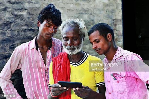 Three People Standing Holding Mobile Phone
