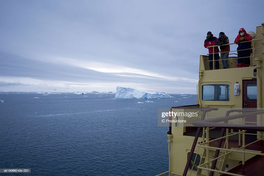 Three people standing on icebreaker ship, looking at view : Stockfoto