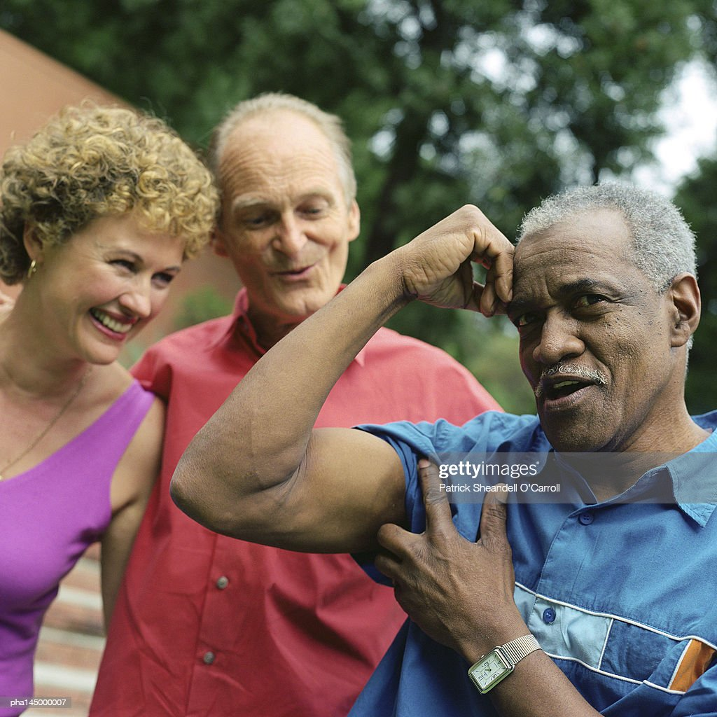 Three people standing outside, man flexing arm muscles : Stockfoto
