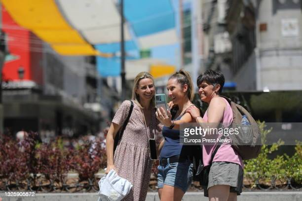 Three people take a photo without a mask in the center of the capital, on June 28 in Madrid, . This is the first working day without the mandatory...